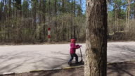 Walk through the park in spring. Girl child riding a scooter on the asphalt path video