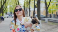 Walk with a puppy in the city. Young woman with a dog on her hands walking in a city park. Steadicam shot video