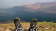 Walker takes rest from Hike - Walking boots overlooking Lake video