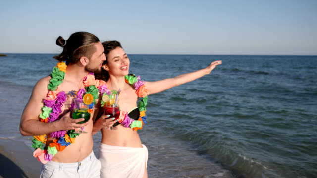 walking couple in love, guy holding girl by hand, an exotic vacation, on background beach panorama, summer, slow motion video