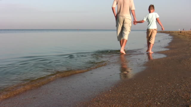 walking father with son on beach video