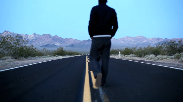 Walking in the middle of a desert road HD video