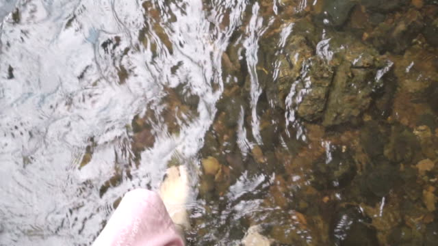 Walking into the shallow water with little rocks under water in waterfall, top view video