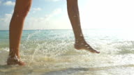 SLOW MOTION CLOSEUP: Walking on sandy beach in shallow water video