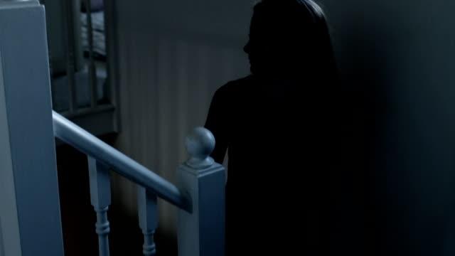 Walking upstairs, entering a dark room. video