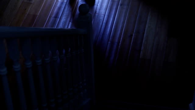 Walking upstairs, man in the dark. video