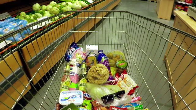 Walking with shopping cart through supermarket point of view shot video