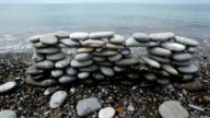 Wall of stones on beach, sea surf in background video