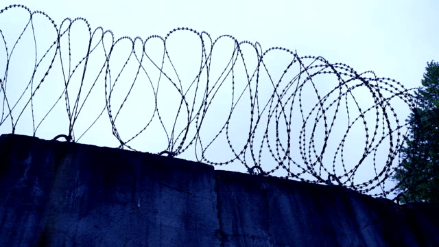 Wall with barbed wire at dawn. video