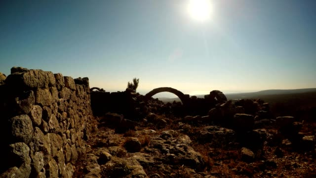 Wall with polygonal laying far Surviving arch among ruins blue sky winter sun Adamkayalar Mersin province Turkey video