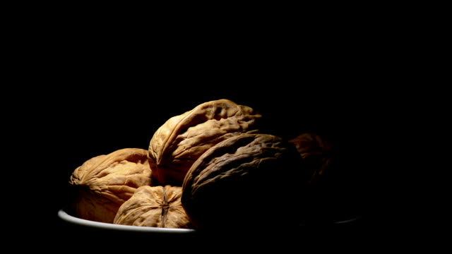 Walnuts food in a bowl in rotation on black background video