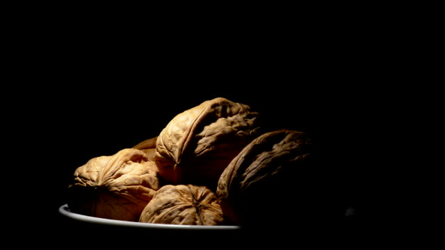 Walnuts nut fruit in a white bowl gyrating on black background video