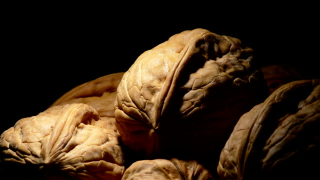 Walnuts rotating on black background with a cenital light video