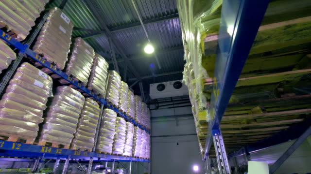 A warehouse corridor sided by shelving units. video