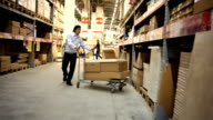 Warehouse. Man comes closer and takes a box. video