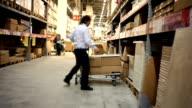 Warehouse. Man takes a box. video