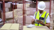 Warehouse worker checking boxes for shipping with tablet pc video