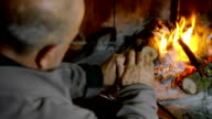 warm up the hands to the fire near the fireplace: wood, flame, tradition, winter video