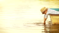 Warmly toned golden footage: wee boy in a trendy hat dangles his hands in the water being in the boat himself. video