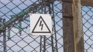 Warning of high voltage on the fence of the power plant. Danger of electric shock. Sign of danger. Electric substation with supports and high-voltage wires. Energy electric industry video