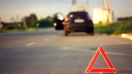 Warning triangle road sign, driver turns hazard lights on, auto-repair services video