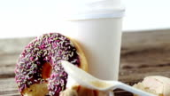 Waste tissue paper, coffee cup and half eaten chocolate doughnut with sprinkles video