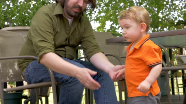 A watchful father sits next to his young child standing next to him video