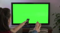 Watching TV, changing channel and coffee, feet up. Chromakey screen. video
