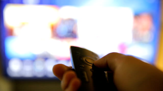 Watching TV-changing channels, blurred TV video