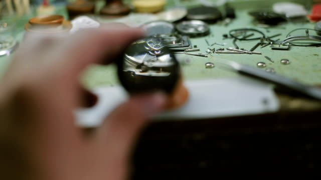 Watchmaker looks through magnifying glass video