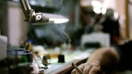 watchmaker smoking cigarette and taking a break from work video