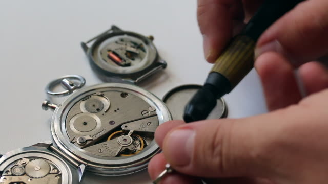 Watchmaking is a master at work. Disassembles the clock using a screwdriver. The watch workshop. Repair of old watches. The mechanism of the clock, the screwdriver, which the master makes repairs, is visible. video