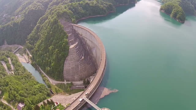 Water accumulation from a river valley in the mountains forming an artificial dam with arched concrete wall video