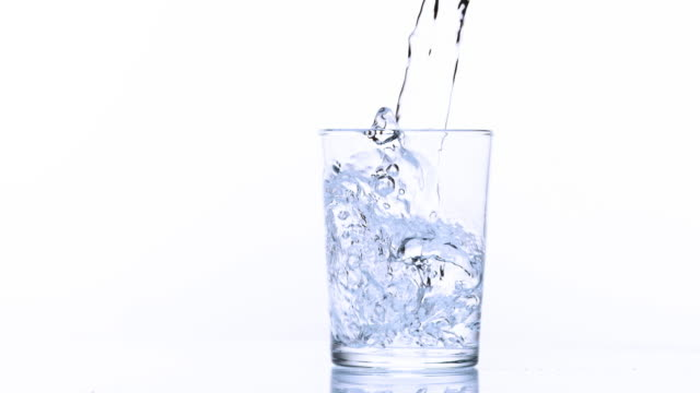 Water being poured into Glass against White Background, Slow Motion 4K video