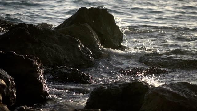 Water Crashing Into Rocks on Beach at Dusk video