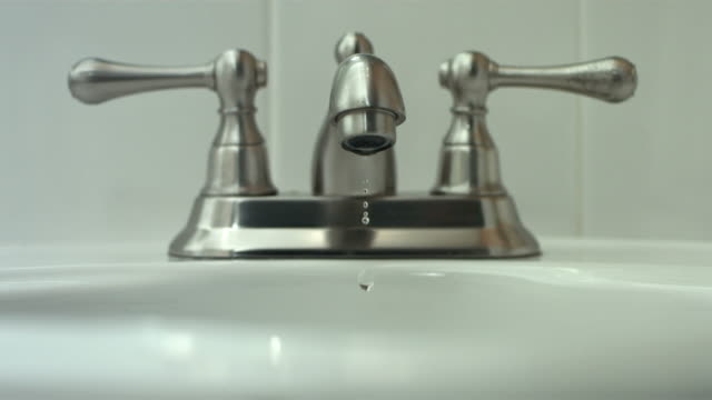 Water drips from faucet, slow motion video