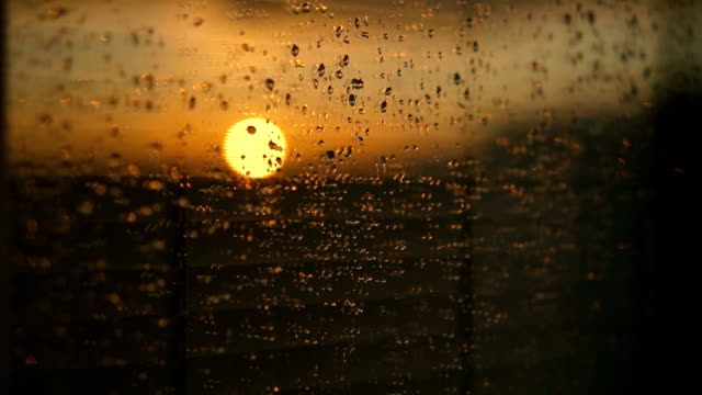 Water drops on a window glass after the rain. The sky with clouds and sun on background. video