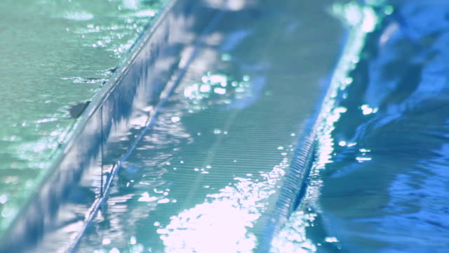 Water filtration system in swimming pool. Water surface near side of pool video