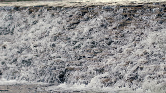 Water flowing over stone cascade. River waterfall in slow motion video