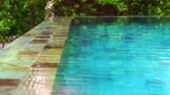 Water flowing overflow on swimming pool edge system. Resort pond with natural stone decoration video