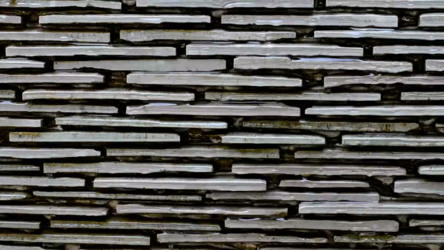 Water flows along a stone wall video