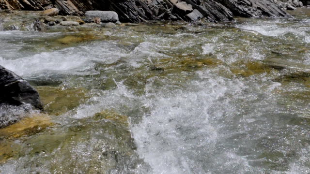 Water in a mountain river in slow motion video. video