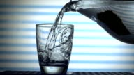 Water poured from a jug into a glass slow motion video