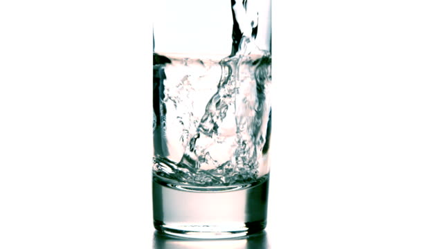 Water pouring into a glass on white background video