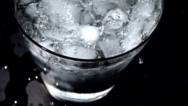 Pouring water into glass of ice with splashes at slow motion on black background video