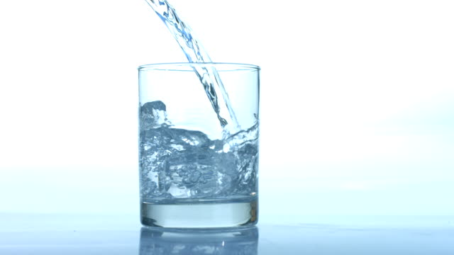 Water pouring into glass, slow motion video