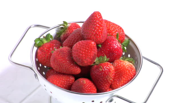 water pouring on colander of strawberries video