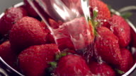Water pouring on strawberries, slow motion video
