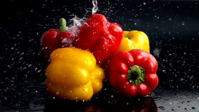 Water pouring on yellow and red peppers in slow motion video