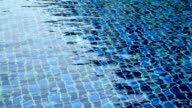 Water ripples and on blue mosaic tiled swimming pool background. video